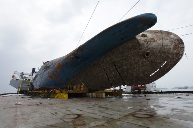 The sunken ferry Sewol sits on a semi-submersible ship during its salvage operations at the sea off Jindo, South Korea, in this handout picture provided by the Ministry of Oceans and Fisheries and released by Yonhap on March 26, 2017. (Photo by Reuters/Yonhap/The Ministry of Oceans and Fisheries)