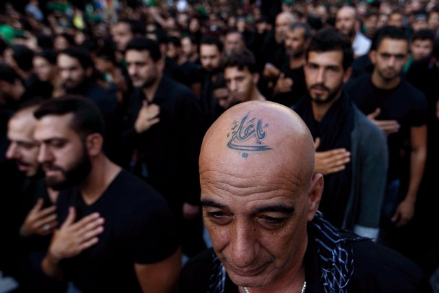 "In this Saturday, Oct. 24, 2015 photo, a Lebanese Shiite supporter of Hezbollah with a tattoo on his head that reads in Arabic, ""Oh Ali"", beats his chest during the holy day of Ashoura, in the southern suburb of Beirut, Lebanon. A growing number of Shiite Muslims in Lebanon are getting tattoos with religious and other Shiite symbols since the civil war in neighboring Syria broke out five years ago, fanning sectarian flames across the region. (Photo by Hassan Ammar/AP Photo)"