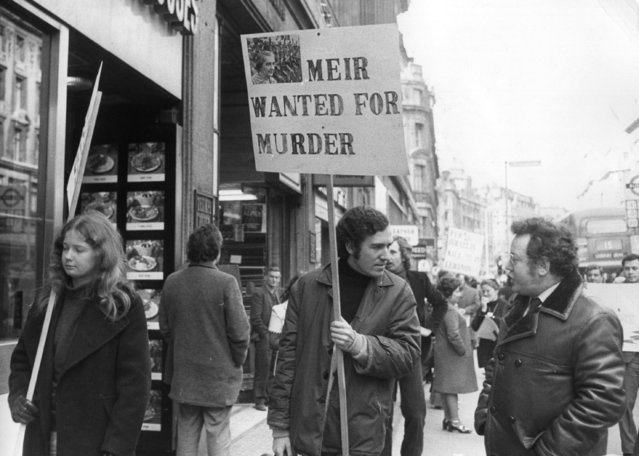 """Peter Hain,  leader of Young Liberals,  heads a demo in a street outside El Al office holding poster (Golda) """"Meir Wanted For Murder"""" after Israeli forces shot down a Libyan airliner. 22nd February 1973. (Photo by Michael Webb/Keystone)"""