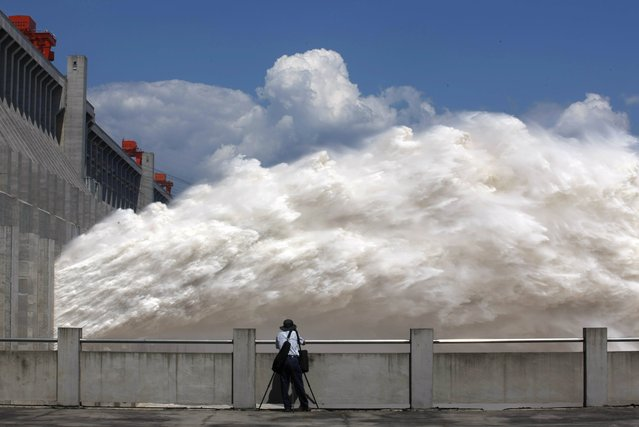 This picture taken on September 3, 2014 shows a man taking pictures of floodwater released from the Three Gorges Dam, a gigantic hydropower project on the Yangtze river, in Yichang, central China's Hubei province, after heavy downpours in the upper reaches of the dam caused the highest flood peak of the year. (Photo by AFP Photo/Stringer)