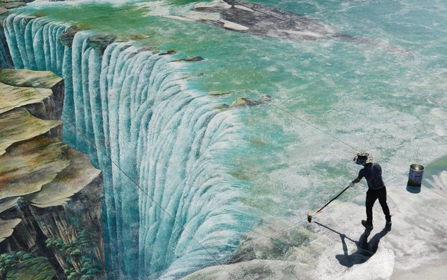 A worker maintains the 3D paintings on the ground at Longgang Scenic Area on April 24, 2020 in Chongqing, China. (Photo by Liu Yang/VCG via Getty Images)