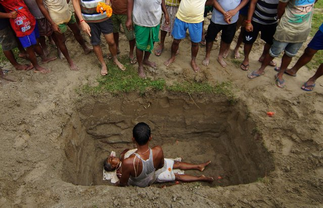 People stand after placing the body of a victim, who was killed during an attack by gunmen at a market on Friday, into a grave during a funeral on the outskirts of Kokrajhar town, in the northeastern state of Assam, India, August 6, 2016. (Photo by Reuters/Stringer)
