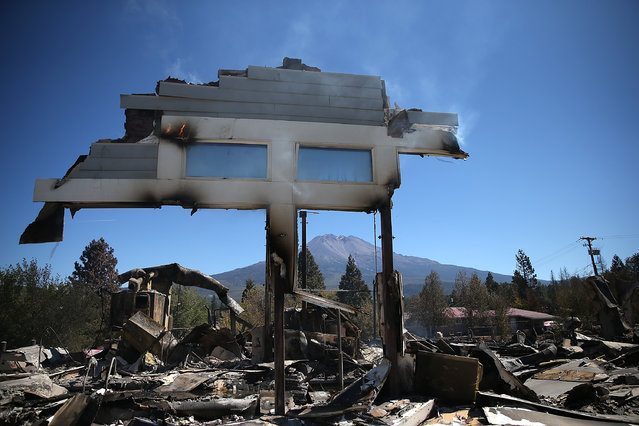 A section of a structure stands over the remains of destroyed business on September 16, 2014 in Weed, California. A fast moving wildfire fueled by high winds ripped through the town of Weed on the afternoon of September 15, burning 100 structures including the high school and lumber mill. (Photo by Justin Sullivan/Getty Images)