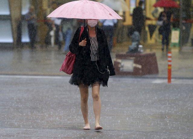 A woman holding an umbrella walks as heavy rain caused by typhoon Etau falls in Tokyo's business district September 9, 2015. (Photo by Toru Hanai/Reuters)