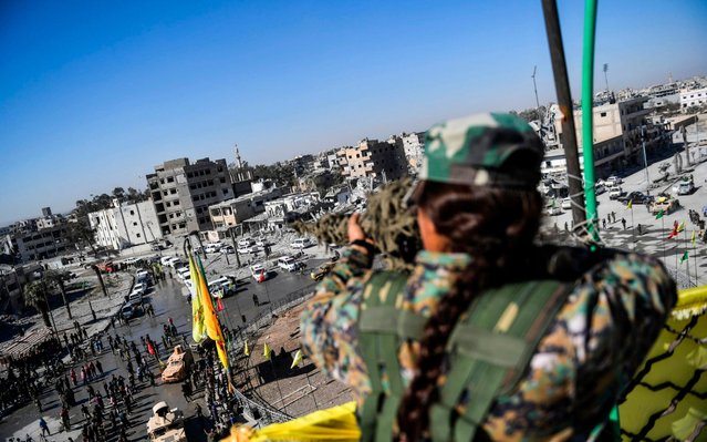 """A female sniper of the Syrian Democratic Forces (SDF) monitors the area during a celebration at the iconic Al- Naim square in Raqa on October 19, 2017, after retaking the city from Islamic State (IS) group fighters. The SDF fighters flushed jihadist holdouts from Raqa' s main hospital and municipal stadium, wrapping up a more than four- month offensive against what used to be the inner sanctum of IS' s self- proclaimed """"caliphate"""". (Photo by Bulent Kilic/AFP Photo)"""