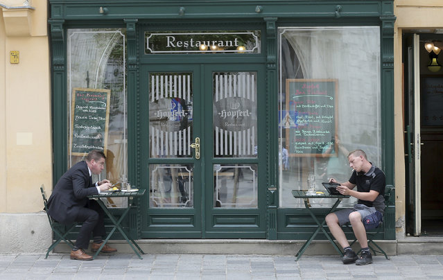 Two guests sit in front of a restaurant with distance in Vienna, Austria, Tuesday, May 19, 2020. The Austrian government has moved to restrict freedom of movement for people, in an effort to slow the onset of the COVID-19 coronavirus. (Photo by Ronald Zak/AP Photo)