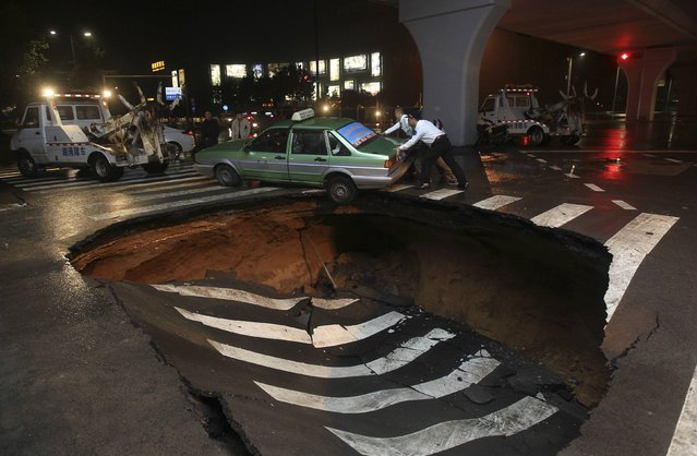 People try to push a taxi which was stuck after a road caved-in in Zhengzhou, Henan province, September 15, 2014. The city authority said due to several days of continuous downpour, two cave-ins occurred along a street in Zhengzhou on Monday. No one was injured during the incidents, local media reported. (Photo by Reuters/Stringer)