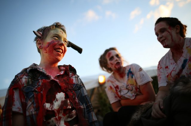 Visitors to the Shocktober Fest dressed as zombies enjoy the occasion at Tulleys Farm  on October 6, 2012 in Turners Hill, England. People dressed as zombies from around the United Kingdom have converged on Tulleys Farm in an attempt to set a new Guinness World Record for the most zombies together in one place.  (Photo by Peter Macdiarmid)