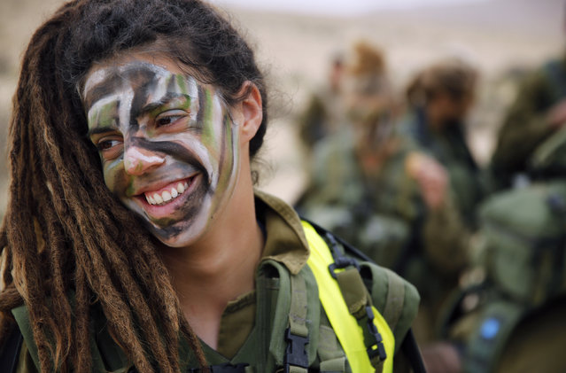 "An Israeli soldier of the Caracal battalion smiles during a 23-kilometer march marking the end of their training in Israel's Negev desert, near Kibbutz Sde Boker February 14, 2013. The ""Caracal"" battalion, two-thirds of whose members are women, was established in 2004 with the purpose of incorporating female soldiers in combat units. The main mission of Caracal is routine patrols on Israel's border with Egypt to intercept infiltrators and smuggling from the Sinai desert. (Photo by Darren Whiteside/Reuters)"