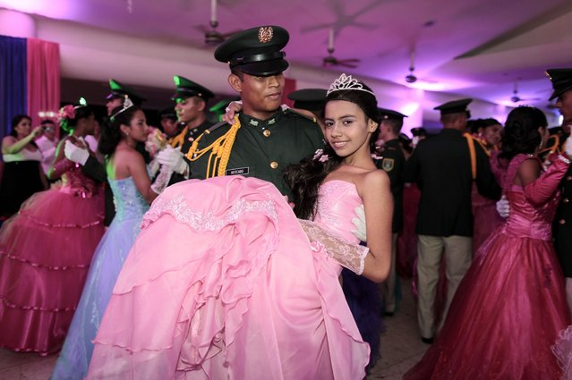 """A cancer patient dances with a cadet from Nicaragua's Military Academy during her """"Quinceanera"""" (15th birthday) party at a hotel in Managua September 20, 2014. A quinceanera is a traditional celebration for a girl turning 15. The Nicaragua's Association of Mother and Father of Children with Leukemia and Cancer (MAPANICA) organizes quinceaneras for cancer patients annually, and there were 44 celebrants in 2014. (Photo by Oswaldo Rivas/Reuters)"""