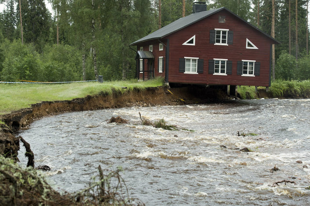 A house, with its foundation washed away, hangs over a rain-swollen creek at Nyhammar in Dalarna, central Sweden, July 10, 2012. (Photo by Leif R. Jansson/Reuters/Scanpix)