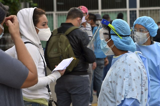 A health worker speaks with people with symptoms of the COVID-19 coronavirus queuing outside a Honduran Institute of Social Secutity (IHSS) unit in Tegucigalpa on June 24, 2020. Honduras is one of the Central American countries worst affected by the coronavirus pandemic with a surge in cases especially in Tegucigalpa and second city San Pedro Sula in the north, and  has so far registered more than 9,000 cases with 322 deaths. (Photo by Orlando Sierra/AFP Photo)