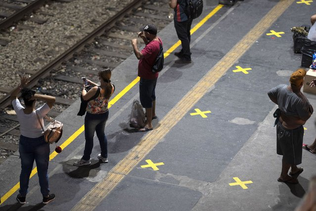Commuters stand next to marks painted on the platform marking social distancing as they wait for the train amid the new coronavirus pandemic in Rio de Janeiro, Brazil, Thursday, June 25, 2020. Authorities say buses can operate with people standing, but limited to 2 commuters per meter square, and marks on the floor will have to be painted in order to help people to keep their distance. (Photo by Leo Correa/AP Photo)