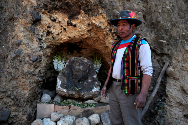 """A witch doctor stands next to relocated stone which bears an impression that locals refer to as """"Devil face"""", as a shrine frequented by indigenous witch doctors is cleared to expand a main highway between La Paz and El Alto, Bolivia, August 24, 2016. (Photo by David Mercado/Reuters)"""