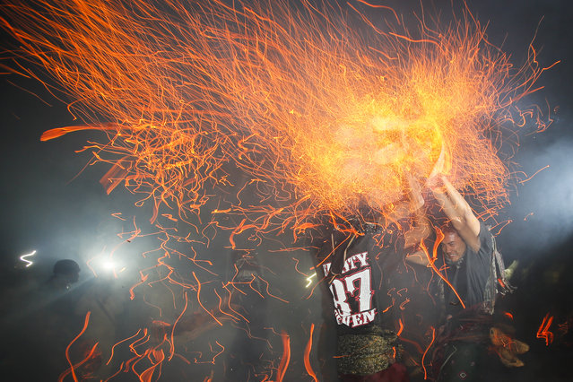 "Balinese men throw fire on each other during a sacred ritual called ""Mesabatan Api"" or a fire fight at a temple in Tuban, Bali, Indonesia, 09 October 2014. October 9, 2014. (Photo by Made Nagi/EPA)"