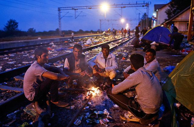 Migrants sit on railway tracks at a train station in Tovarnik, Croatia, September 20, 2015. (Photo by Antonio Bronic/Reuters)
