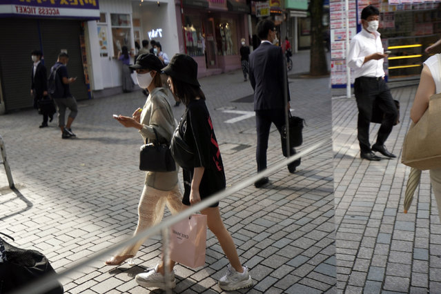 People wearing protective masks to help curb the spread of the new coronavirus are reflected on a mirror at a shopping street in Tokyo Friday, June 26, 2020. (Photo by Eugene Hoshiko/AP Photo)