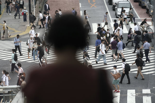 People wearing a protective face mask to help curb the spread of the coronavirus walk at Shibuya pedestrian crossing Thursday, July 9, 2020, in Tokyo. The Japanese capital has confirmed more than 220 new coronavirus infections, exceeding its previous record. (Photo by Eugene Hoshiko/AP Photo)