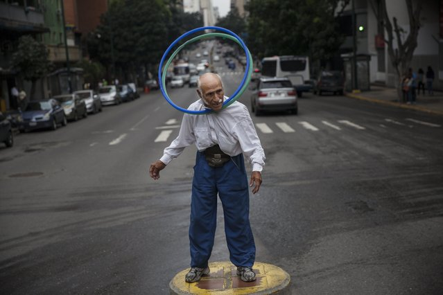 """Jose Bestilleiro, 83, from Spain, performs for tips at an street intersection in downtown Caracas, Venezuela, Sunday, October 29, 2017. Bestilleiro said he's been performing every day for the past 15 years, and brings in at least 5,000 Bolivars a day, which on the black market is 11 cents and is the price of a cheap """"arepa"""" sandwich. (Photo by Rodrigo Abd/AP Photo)"""