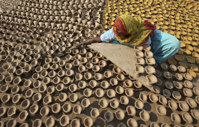 A woman puts out earthen lamps to dry in the sun at her workshop ahead of the Hindu festival of Diwali in Chandigarh October 23, 2013. (Photo by Ajay Verma/Reuters)