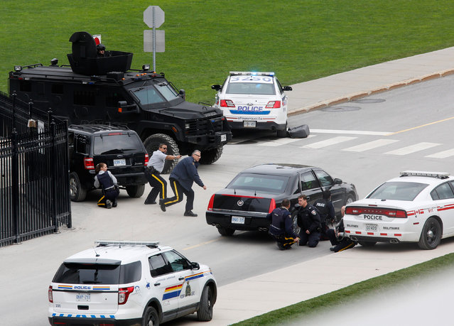 Police officers take cover near Parliament Hill following a shooting incident in Ottawa October 22, 2014. (Photo by Chris Wattie/Reuters)