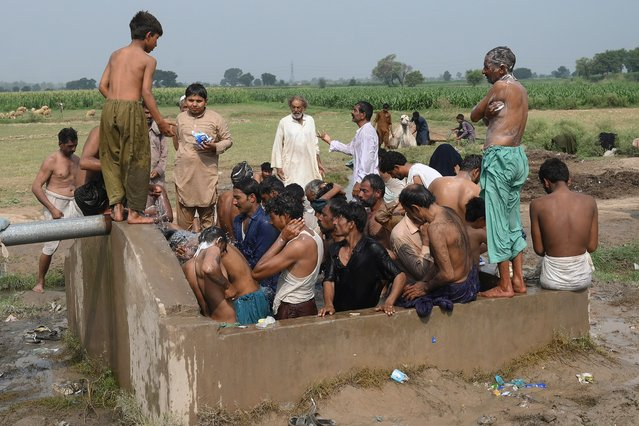 """Farmers and vendors take bath at a cattle market set to buy sacrificial animals ahead of Eid al-Adha Muslim festival or the """"Festival of sacrifice"""" in Lahore on July 26, 2020. Eid al-Adha, feast of the sacrifice, marks the end of the Hajj pilgrimage to Mecca and commemorates Prophet Abraham's readiness to sacrifice his son to show obedience to Allah. (Photo by Arif Ali/AFP Photo)"""