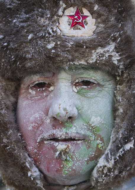 """A military dressed man with flour and eggs on his face looks on as he takes part in the battle of """"Enfarinats"""", a floor fight in the town of Ibi, in the south-eastern Spain on December 28, 2012. For 200 years Ibi's citizens annually celebrate with a battle using flour, eggs and firecrackers outside the city townhall. (Photo by Jaime Reina/AFP Photo)"""