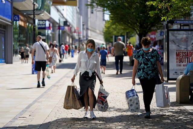 People walk wearing face masks to try to stop the spread of coronavirus in a shopping area in Manchester, northern England, Friday, July 31, 2020. The British government on Thursday night announced new rules on gatherings in some parts of Northern England, including Manchester, that people there should not mix with other households in private homes or gardens in response to an increase trend in the number of cases of coronavirus cases per 100,000 people. (Photo by Jon Super/AP Photo)