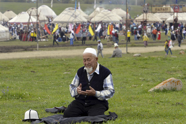 In this photo taken on photo taken on Sunday, September 4, 2016, a Kyrgyz man prays during the second World Nomad Games at Issyk Kul lake in Cholpon-Ata, Kyrgyzstan. (Photo by Vladimir Voronin/AP Photo)