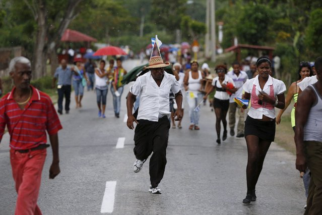 People run from the rain after Pope Francis drove past in El Cobre, Cuba, September 21, 2015. (Photo by Carlos Garcia Rawlins/Reuters)