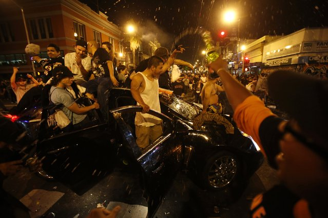 Revellers celebrate from a moving vehicle in San Francisco, California October 29, 2014. (Photo by Stephen Lam/Reuters)