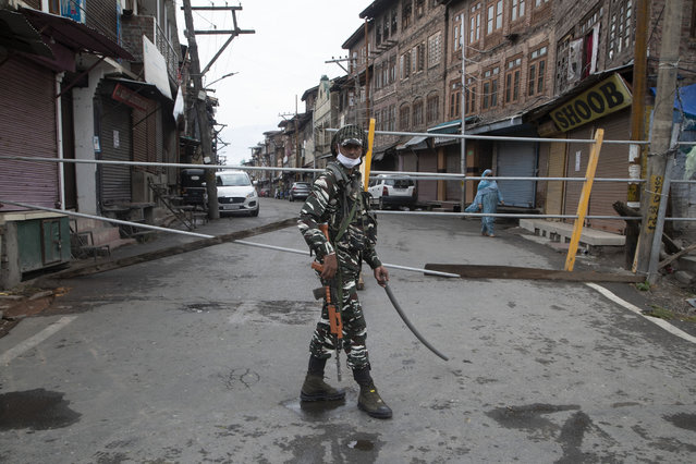 An Indian paramilitary soldier stands guard by a closed road, as Kashmiris marked Eid during lockdown to curb the spread of coronavirus in in Srinagar, Indian controlled Kashmir, Saturday, August 1, 2020. Eid al-Adha, or the Feast of the Sacrifice, is marked by sacrificing animals to commemorate the prophet Ibrahim's faith in being willing to sacrifice his son. (Photo by Mukhtar Khan/AP Photo)