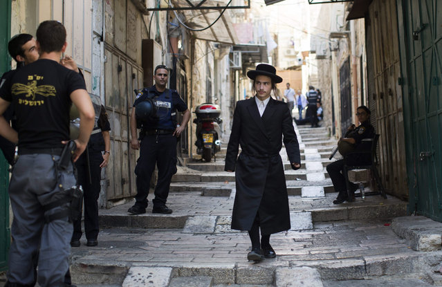 An Ultra orthodox Jew passing Israeli Police on patrol in an alley of the old city of Jerusalem, 04 October 2015. Israeli police imposed tight security in the Old City of Jerusalem, and banned prayer in Al-Aqsa for those under the age of 50 for men, for two days, following the killing of two Israelis in the two attacks, and the wounding of three others including a child. (Photo by Atef Safadi/EPA)