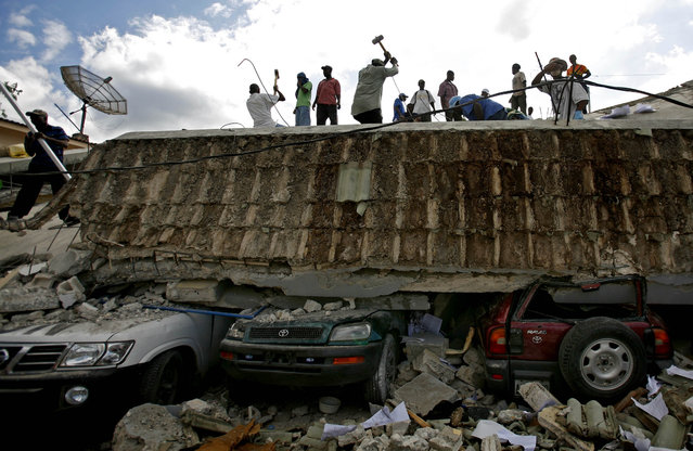 People search for survivors under the rubble of a collapse building the day after an earthquake hit Port-au-Prince, Haiti, Wednesday, January 13, 2010. (Photo by Ricardo Arduengo/AP Photo)