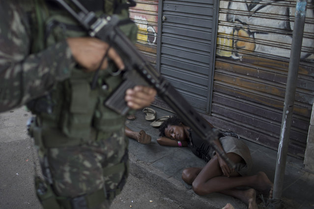 A soldier walks past people sleeping on the sidewalk as he takes part in a surprise operation in the Jacarezinho slum in Rio de Janeiro, Brazil, Thursday, January 18, 2018. (Photo by Leo Correa/AP Photo)