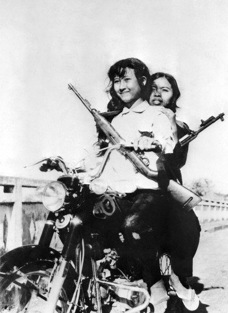Women soldiers ride a Japanese motorcycle in the streets of the Cambodian capital of Phnom Penh, in April 1975.  On New Year's Day 1975, Communist troops led by Pol Pot and Ieng Sary, launched an offensive to oust Lon Nol's Khmer Republic. The Lon Nol governement in Phom Penh surrendered 17 April 1975 after 117 days of the hardest fighting of the war. Immediately after its victory, the PCK ordered the evacuation of all cities and towns. Many of the foreigners and some Cambodians, who couldn't or wouldn't flee Cambodia, took refuge at the embassy from which they were taken by truck to Thailand two weeks later. (Photo by STF/AFP Photo)