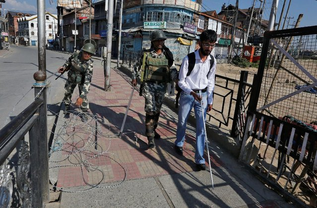 An Indian policeman helps a visually impaired man to cross a concertina wire laid on a pavement during a curfew in Srinagar September 19, 2016. (Photo by Danish Ismail/Reuters)