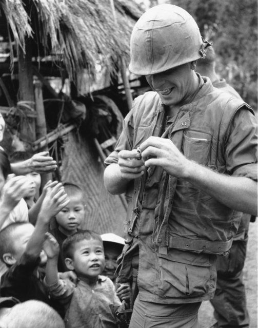 Cpl. W.L Files of Charleston, WV, distributes his candy supply amongst these Vietnamese children who were being evacuated from their village near An Hoa on December 19, 1967 during the Vietnam War. (Photo by AP Photo)