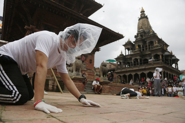 In this June 30, 2020, file photo, Nepalese youth perform a play as part of a protest demanding better COVID-19 management at Patan Durbar Square near Kathmandu, Nepal. (Photo by Niranjan Shrestha/AP Photo/File)