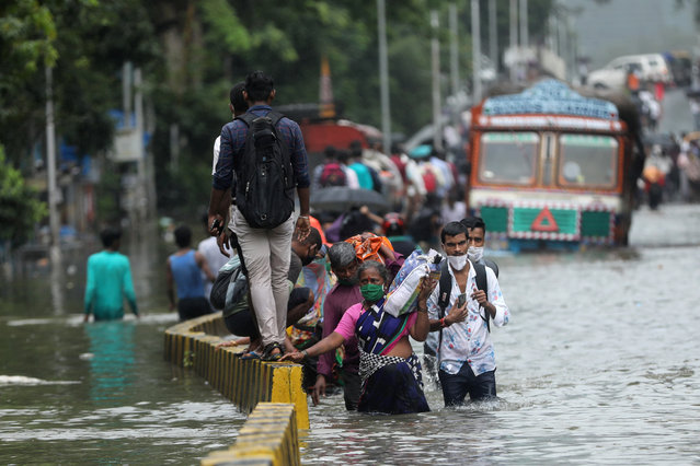 People wade through a waterlogged road after heavy rainfall in Mumbai, India, September 23, 2020. (Photo by Francis Mascarenhas/Reuters)