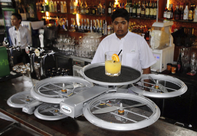 A bartender watches as an Infinium-Serve Flying Robot takes off with an order at a restaurant during a pilot demonstration for the media in Singapore, February 5, 2015. (Photo by Edgar Su/Reuters)