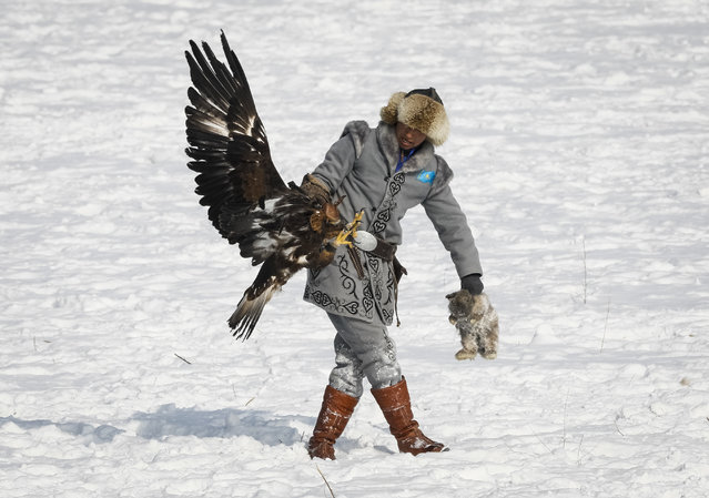 A hunter walks with a rabbit, caught by his tamed golden eagle during an annual hunters competition at Almaty hippodrome, Kazakhstan February 9, 2018. (Photo by Shamil Zhumatov/Reuters)