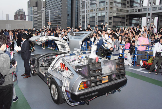 """DeLorean, remodeled similar to the """"Back to the Future Part II"""" time machine, that runs on bioethanol fuel made from old clothes, is shown to fans during a special celebration event organized by NBC Universal Entertainment Japan to mark the 30th anniversary of the sci-fi film's debut, in Tokyo Wednesday, October 21, 2015. (Photo by Ayaka Aizawa/Kyodo News via AP Photo)"""