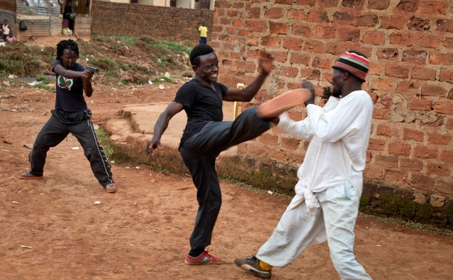 """In this photo taken Wednesday, September 7, 2016, actors rehearse at the """"Wakaliwood"""" studios in the Wakaliga slum of Kampala, Uganda. Deep in this Kampala slum at a tin-roofed collection of houses known as Wakaliwood, is the engine of Uganda's tiny film industry and the source of $200-budget movies and a glimmer of fame. (Photo by Stephen Wandera/AP Photo)"""