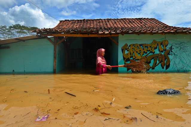 A woman villager cleans garbage in front of her house as flood hits Tanjungsari village in Tasikmalaya, Indonesia, February 23, 2018. (Photo by Adeng Bustomi/Reuters/Antara Foto)