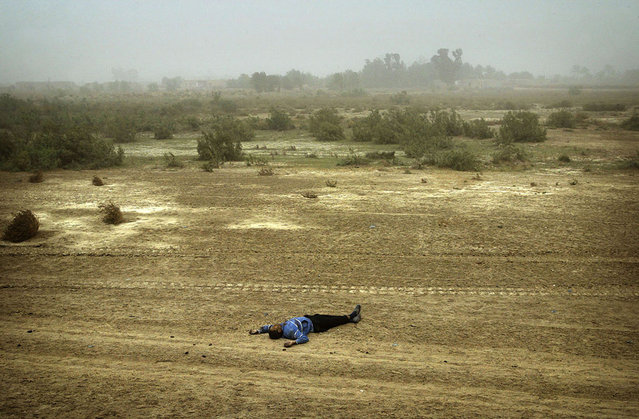 A body of Iraqi man lies by the road side north of Al Nassiriyah, on March 25, 2003. More than 30 men of military age were killed on the key northern highway by an apparent U.S. air strike on the vehicles carrying the Iraqis. (Photo by Damir Sagolj/Reuters/The Atlantic)