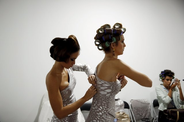 "Angela Ponce, 24, (R) gets help from a fellow contestant getting dressed to compete in the ""Miss World Spain"" pageant in Estepona, southern Spain, October 25, 2015. (Photo by Susana Vera/Reuters)"