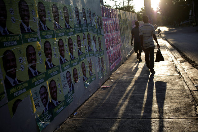 People walk next to electoral posters plastered on a wall in a street of Port-au-Prince, Haiti, September 26, 2016. (Photo by Andres Martinez Casares/Reuters)