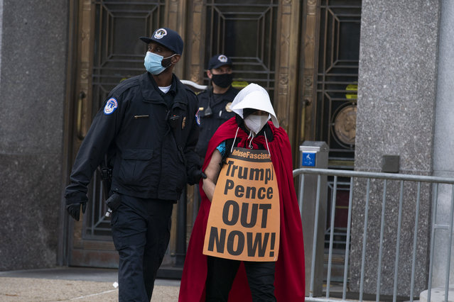 """Demonstrators opposed to the confirmation of President Donald Trump's Supreme Court nominee, Judge Amy Coney Barrett, dressed as characters from """"The Handmaid's Tale"""", are arrested after blocking an entrance of the Dirksen Senate office building, Thursday, October 22, 2020, on Capitol Hill in Washington. (Photo by Jose Luis Magana/AP Photo)"""