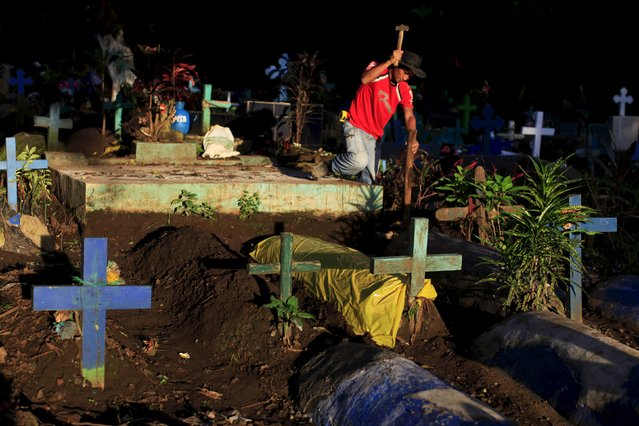A man cleans the grave of a relative during celebration of the Day of the Dead in Nahuizalco, El Salvador November 2, 2015. (Photo by Jose Cabezas/Reuters)